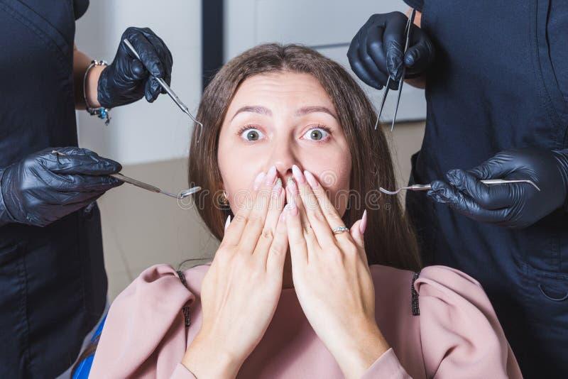 tand- klinik Mottagande undersökning av patienten Tandomsorg Den unga kvinnan känner skräck på tandläkaren fotografering för bildbyråer