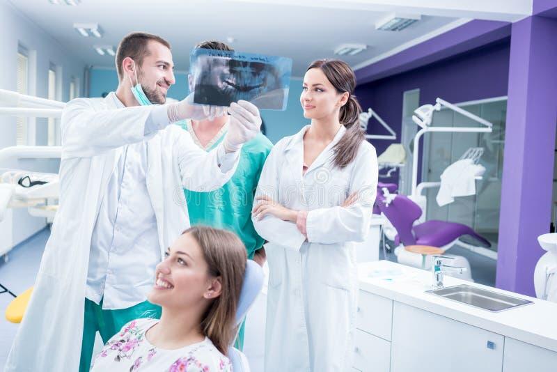 Tand- medicinskt lag som undersöker och arbetar på den unga ¸female patien royaltyfria bilder