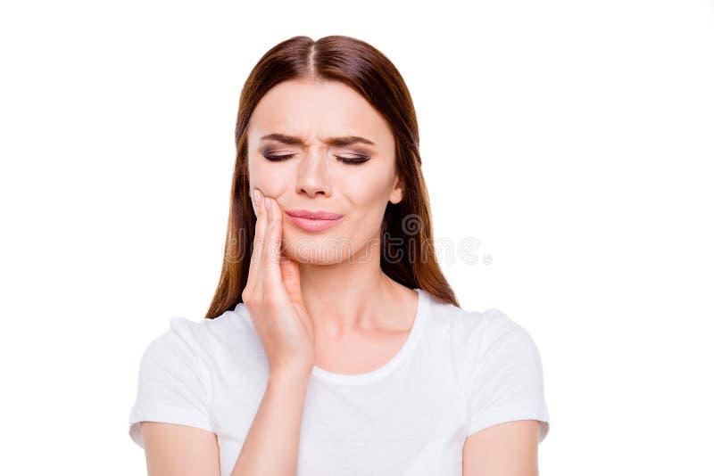 Tand- vård- begrepp Stående av den ledsna brunhåriga unga kvinnan och att ha stark tandvärk som isoleras på vit bakgrund, i vit c arkivfoto