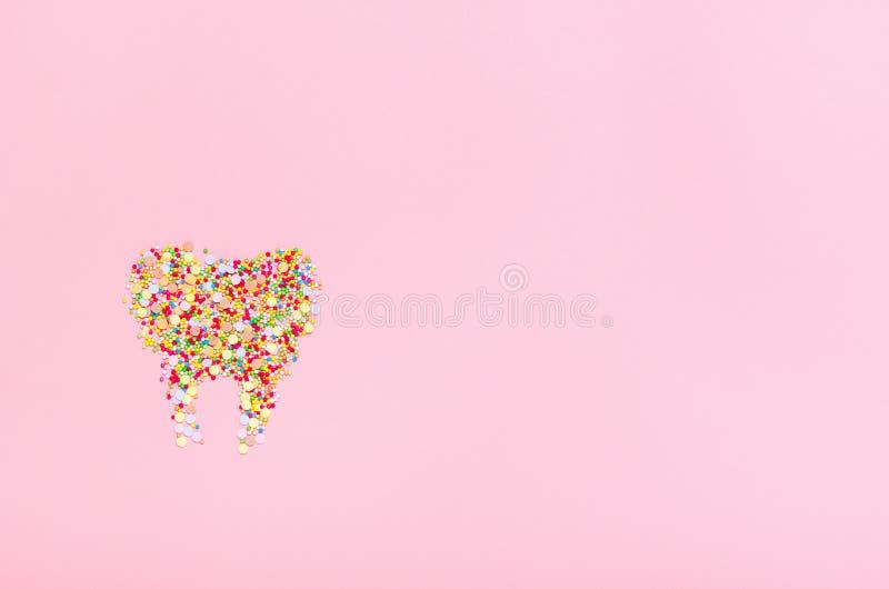 Tand van banketbakkerij die zich op een roze achtergrond kleedt Het concept schadelijke snoepjes, tandgezondheid en glimlachen ex royalty-vrije stock afbeeldingen