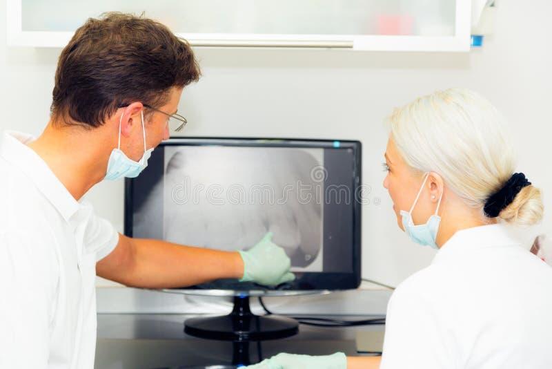 Tandarts And Assistant Looking bij Tandröntgenstraal royalty-vrije stock afbeelding