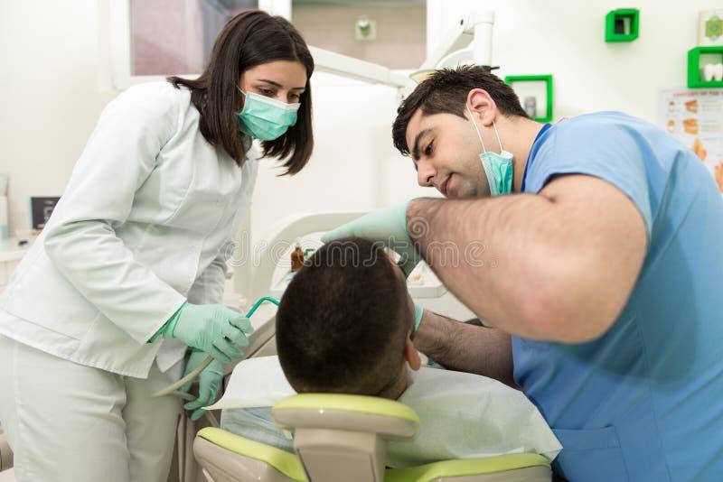 Tandarts Curing een Mannelijke Patiënt stock afbeeldingen