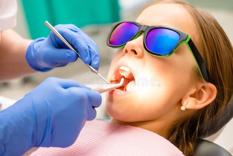 Tandarts die de elementaire tanden van leeftijdsmeisjes met tandhulpmiddelen in pediatrische tandkliniek onderzoeken stock foto