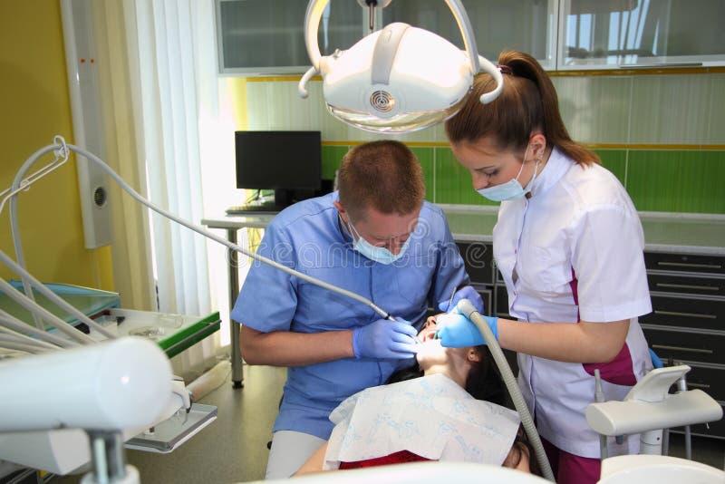 Tandarts die de geduldige tanden van ` behandelen s met tandhulpmiddelen in tandkliniek tandheelkunde stock afbeeldingen