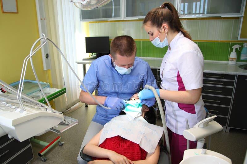 Tandarts die de geduldige tanden van ` behandelen s met tandhulpmiddelen in tandkliniek tandheelkunde stock foto's