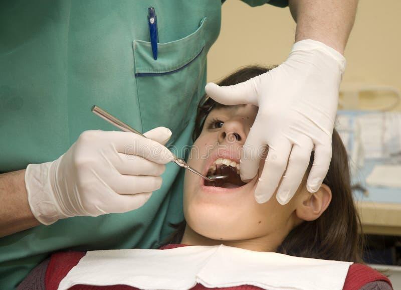 Tandarts die de tanden van een meisje onderzoekt royalty-vrije stock foto's