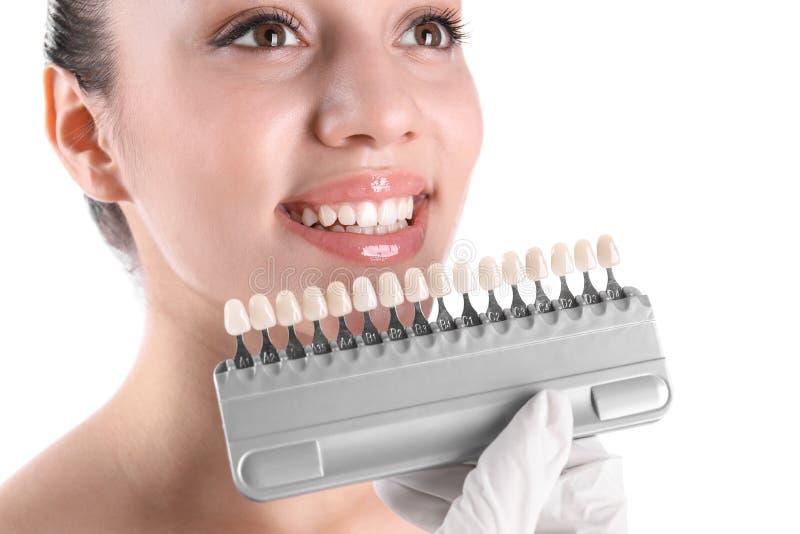 Tandarts die de tandenkleur controleren van de jonge vrouw royalty-vrije stock afbeelding