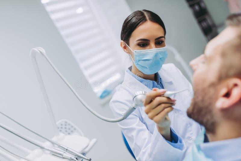 Tandarts die geduldige tanden behandelen stock foto