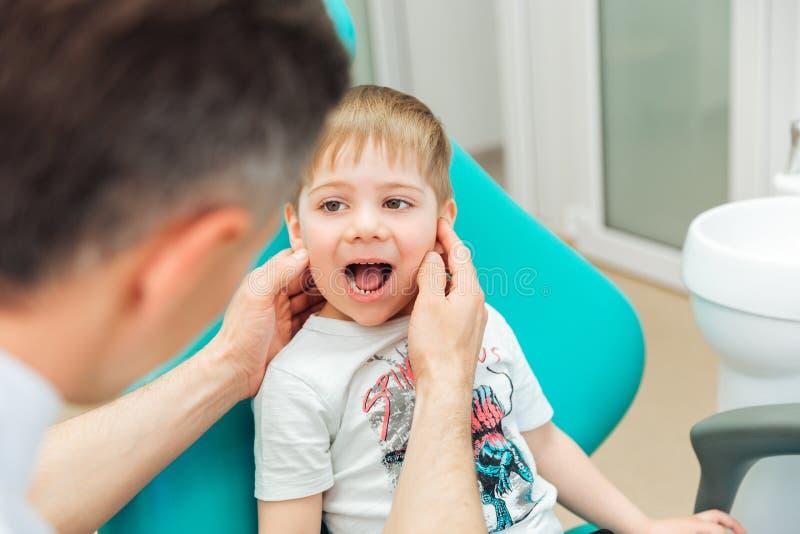 Tandarts die tanden van weinig jongenszitting onderzoeken met geopende mond stock afbeeldingen