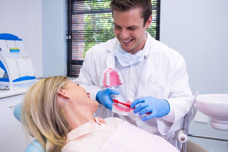 Tandarts die tandvorm door vrouw houden bij kliniek royalty-vrije stock afbeeldingen
