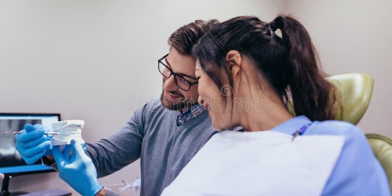 Tandarts die tandzorg aantonen aan patiënt stock fotografie