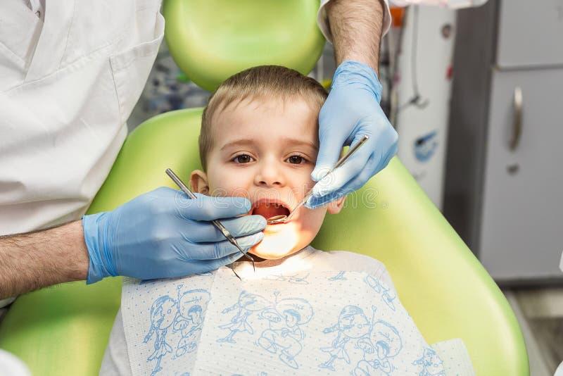 Tandarts die weinig jongens` s tanden in kliniek onderzoeken Tandprobleem royalty-vrije stock foto