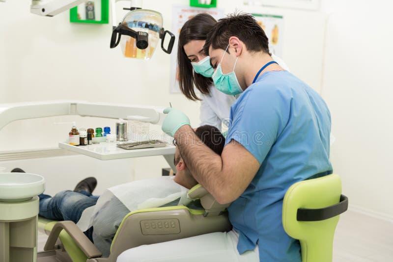 Tandarts Doing een Tandbehandeling op Patiënt stock fotografie