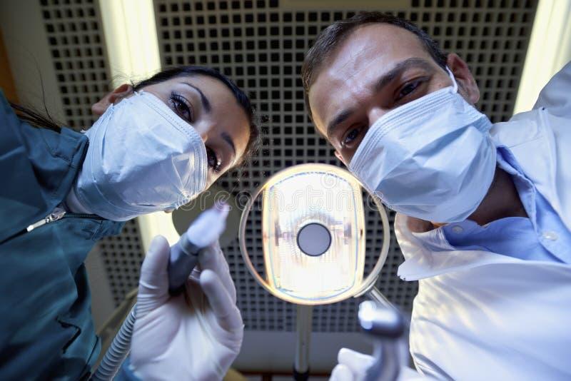 Tandarts en medewerker het werken en het vullen tand aan zieke patiënt royalty-vrije stock foto's