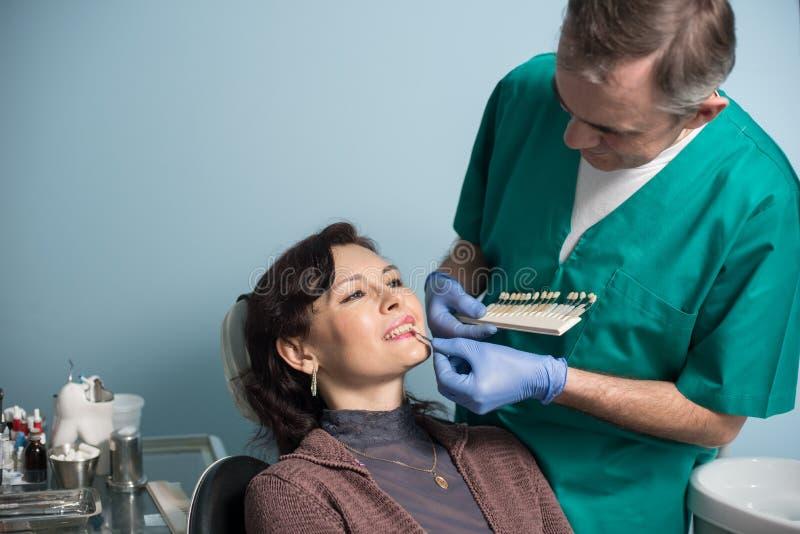 Tandarts en vrouwelijke patiënt die en kleur van de tanden in tandkliniekbureau controleren selecteren tandheelkunde royalty-vrije stock foto's