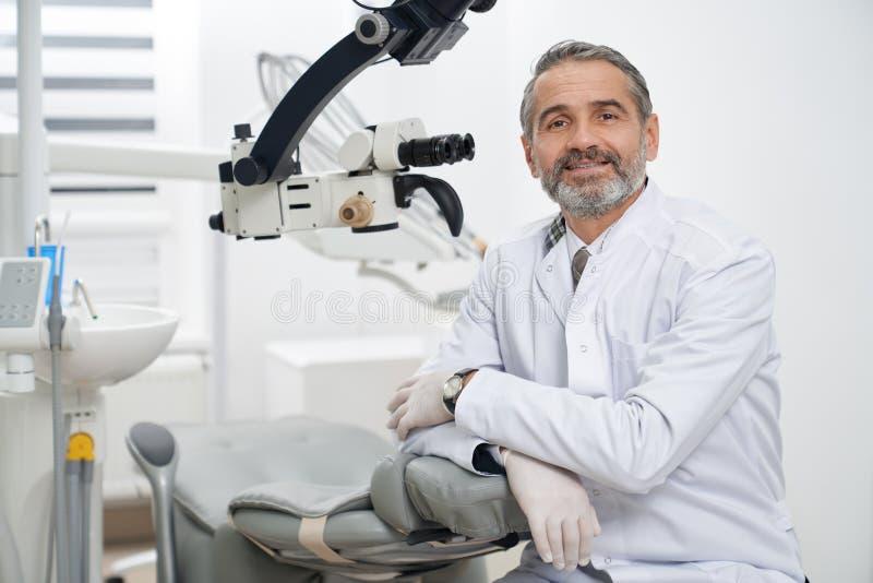 Tandarts het stellen op werkplaats in moderne kliniek royalty-vrije stock afbeelding