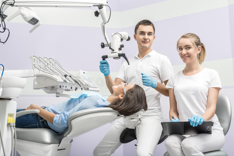 Tandarts, medewerker en patiënt in kliniek royalty-vrije stock foto