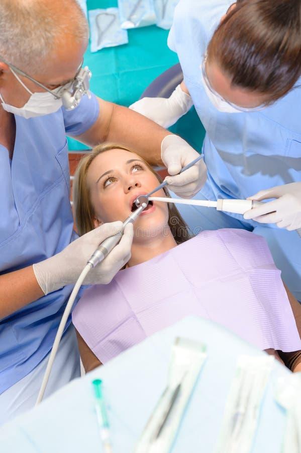 Tandarts met verpleegster die procedure aangaande patiënt doet royalty-vrije stock afbeelding