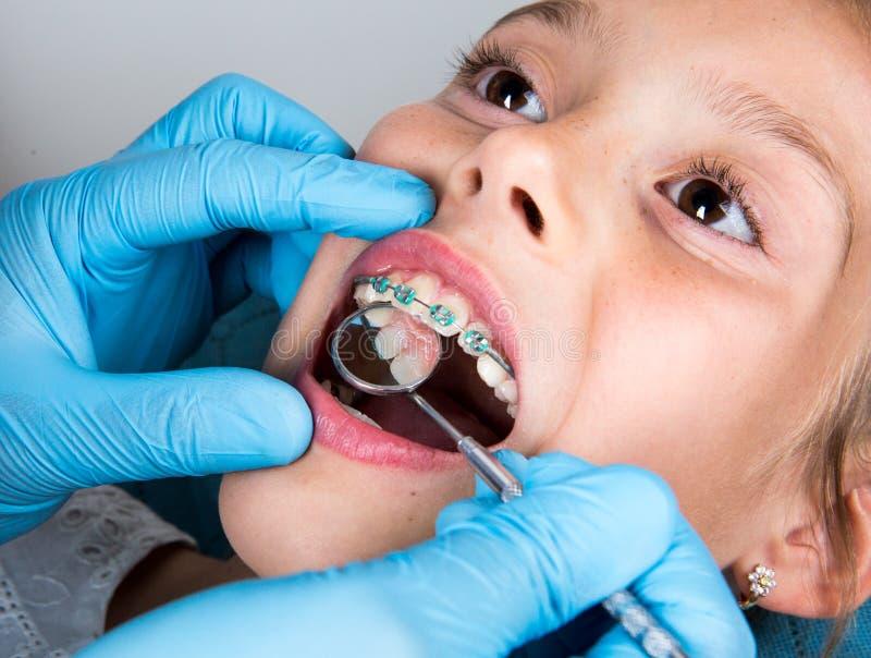 Tandarts, Orthodontist die kleine meisjes geduldige ` s tanden onderzoeken stock fotografie