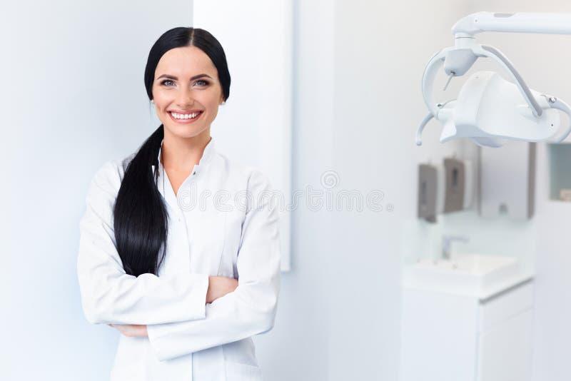 Tandarts Portrait Vrouw die op het haar Werk glimlachen Tand kliniek stock foto