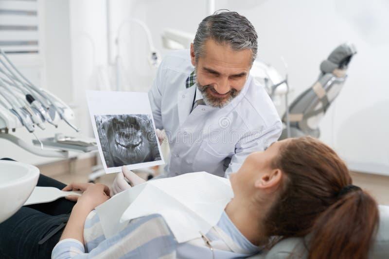 Tandarts raadplegende patiënt over tandröntgenstraal stock foto's