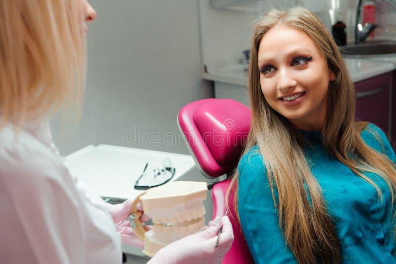 Tandarts in tandbureau die met een patiënt spreken en voor behandeling voorbereidingen treffen stock foto