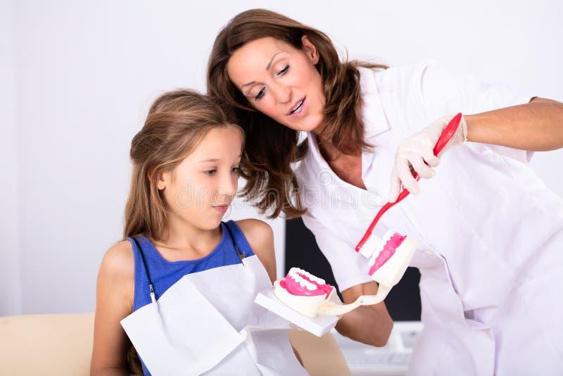 Tandarts Teaching Patient How om de Tanden te borstelen stock afbeeldingen