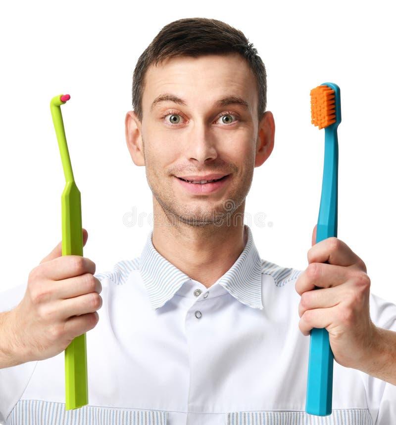 Tandarts vergelijken de artsen tandhygiënisten twee grote tandenborstels royalty-vrije stock afbeelding