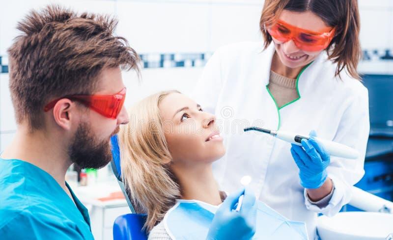Tandartsen die tandverbinding met ultraviolette lamp aansteken royalty-vrije stock foto