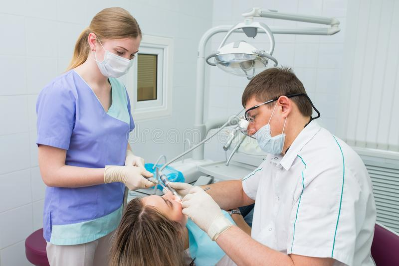 Tandartsen en medewerker die tanden van vrouwenpatiënt behandelen royalty-vrije stock afbeelding