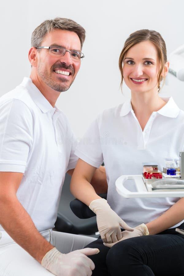 Tandartsen in hun chirurgie of bureau met tandhulpmiddelen stock afbeelding