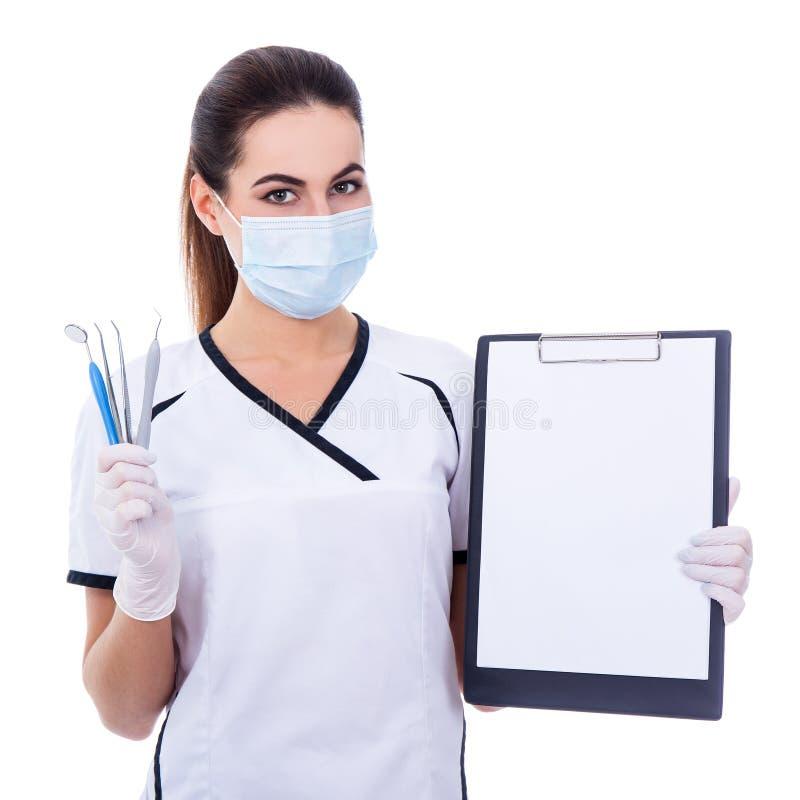 Tandartsvrouw in de hulpmiddelen van de maskerholding en klembord met lege pap stock foto