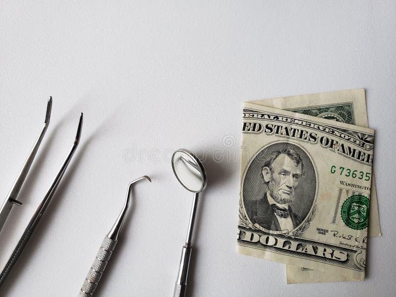 tandartswerktuigen voor mondeling overzicht en Amerikaans bankbiljet van dollar vijf royalty-vrije stock afbeelding