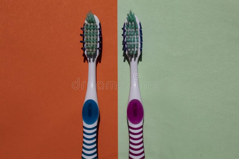 2 tandborstar, blått och rosa Isolerat på grön och orange bakgrund arkivbild