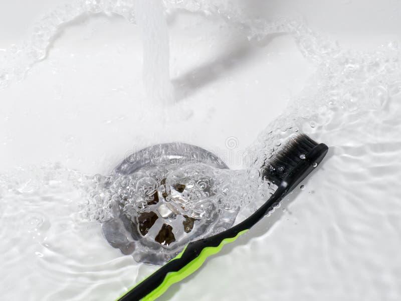 Tandborste som ligger i vasken med rinnande vatten royaltyfri bild