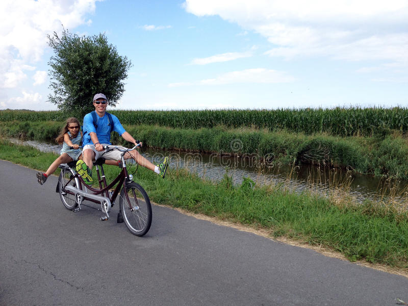 Tandem biking. Picture of father and daughter on a tandem bike in West-Vlaanderen,Belgium stock photo