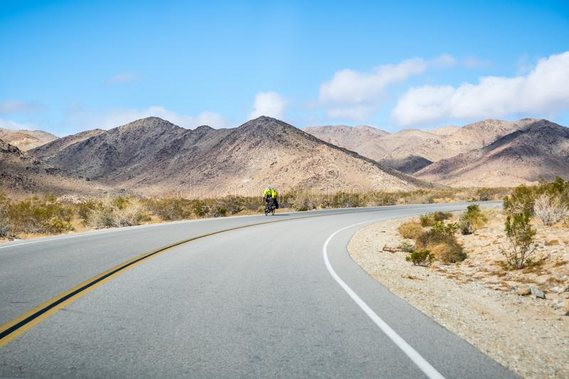 Tandem Cycling on one of roads in Joshua Tree National Park; rocky mountains in the background, south California stock image