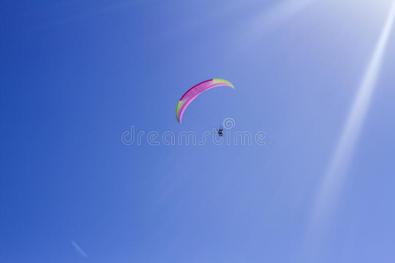 Tandem de l'instructeur et du débutant sur un parapentiste dans un ciel bleu lumineux images stock