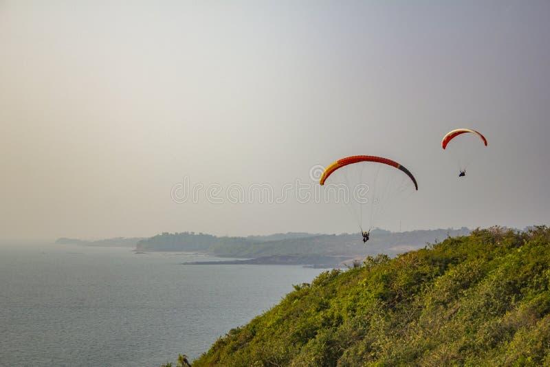 tandem des parapentistes sur un parachute rouge jaune et une mouche pilote simple au-dessus de la mer et d'une colline verte photos libres de droits