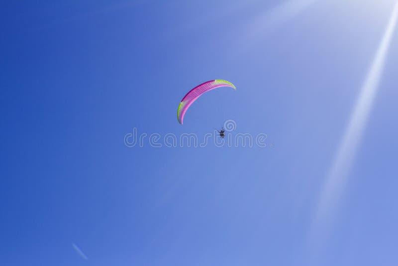 Tandem do instrutor e do novato em um paraglider em um céu azul brilhante imagens de stock