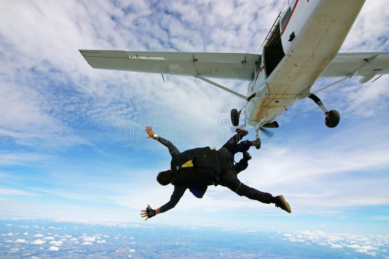 Tandem im freien Fall springend, springen Sie von der Fläche heraus stockfotografie