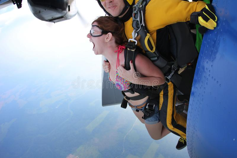 Tandem skydiving. Exit. Girl is screaming. stock image