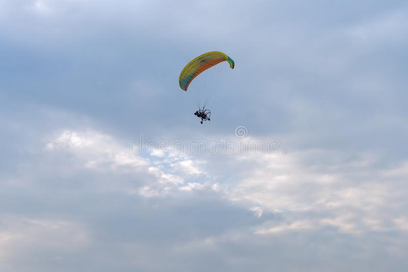 A tandem motor paraglider flies through the evening cloudy sky with a pilot and a passenger. royalty free stock photo