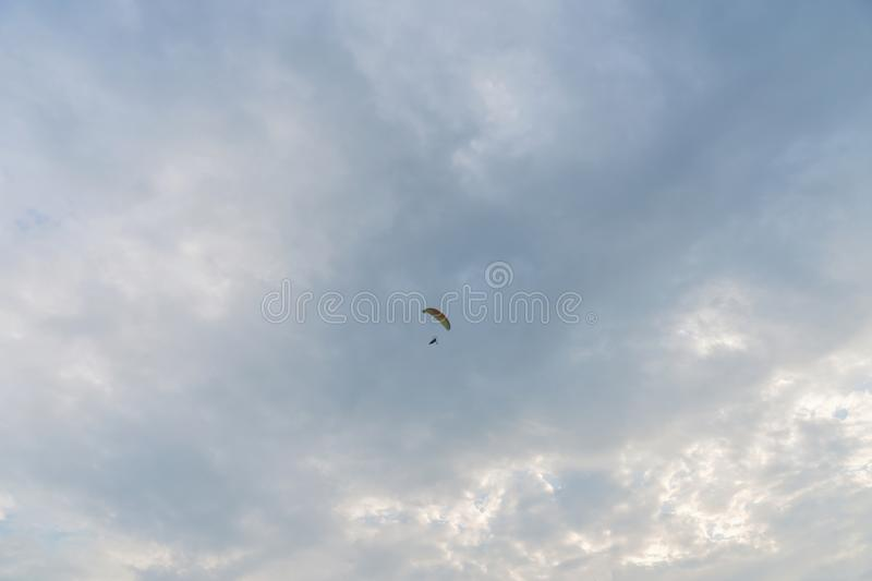 Tandem motor paraglider flying high in the evening cloudy sky with a pilot and a passenger stock image