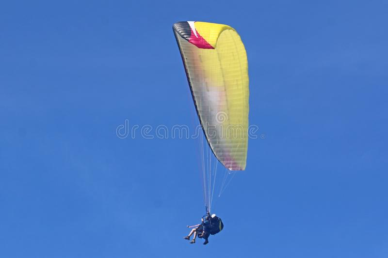 Tandem paraglider in a blue sky stock images