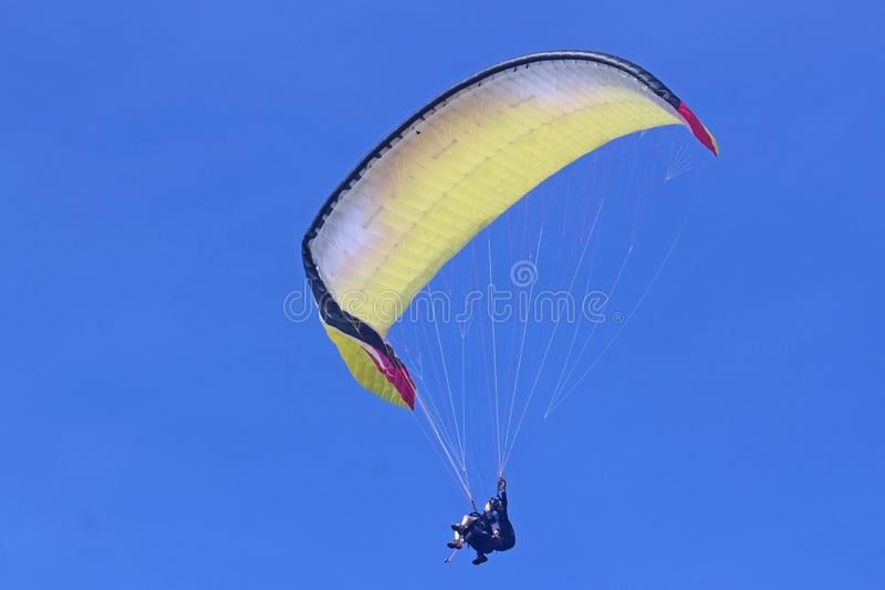 Tandem paraglider flying yellow wing stock photo