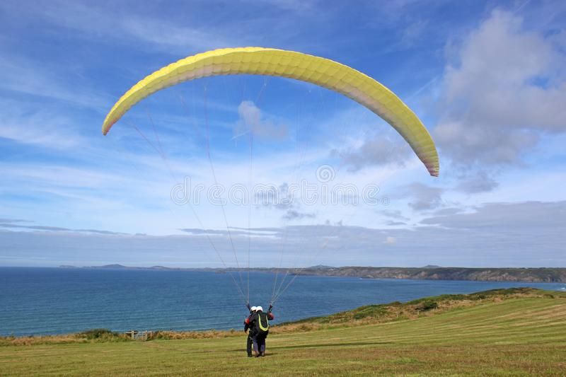 Tandem paraglider launching at Newgale. Tandem paraglider launching above Newgale Bay in Wales royalty free stock photography