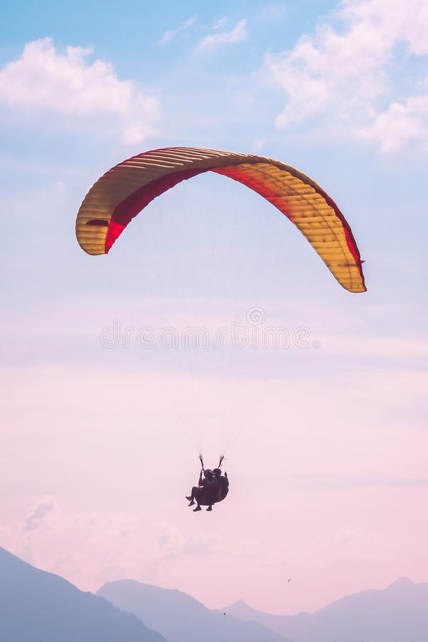 Tandem paragliders flying in sunset over Interlaken in Switzerland. Silhouettes of Swiss Alps, pink sunset sky. Adventurous royalty free stock photography