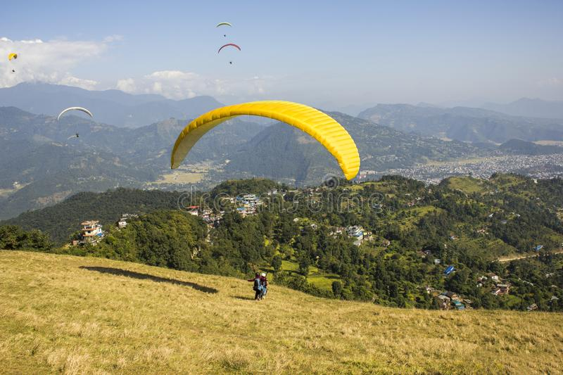 A tandem paragliders on a yellow parachute during takeoff from the hillside against the background of green mountains and the city stock images
