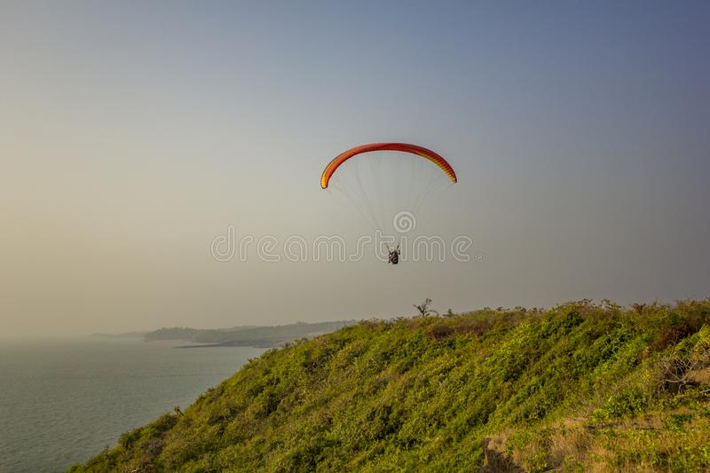 Tandem paragliders on a yellow red parachute fly over the sea and green grass against a clean gray blue sky royalty free stock images